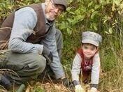 This is a photo of a dad and his young son planting trees.