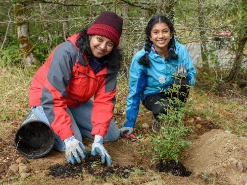 This is an image of a mother and daughter planting a tree.