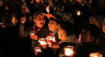 This is a picture of Girl and Boy Scouts laughing and holding candles in celebration of Earth Hour.