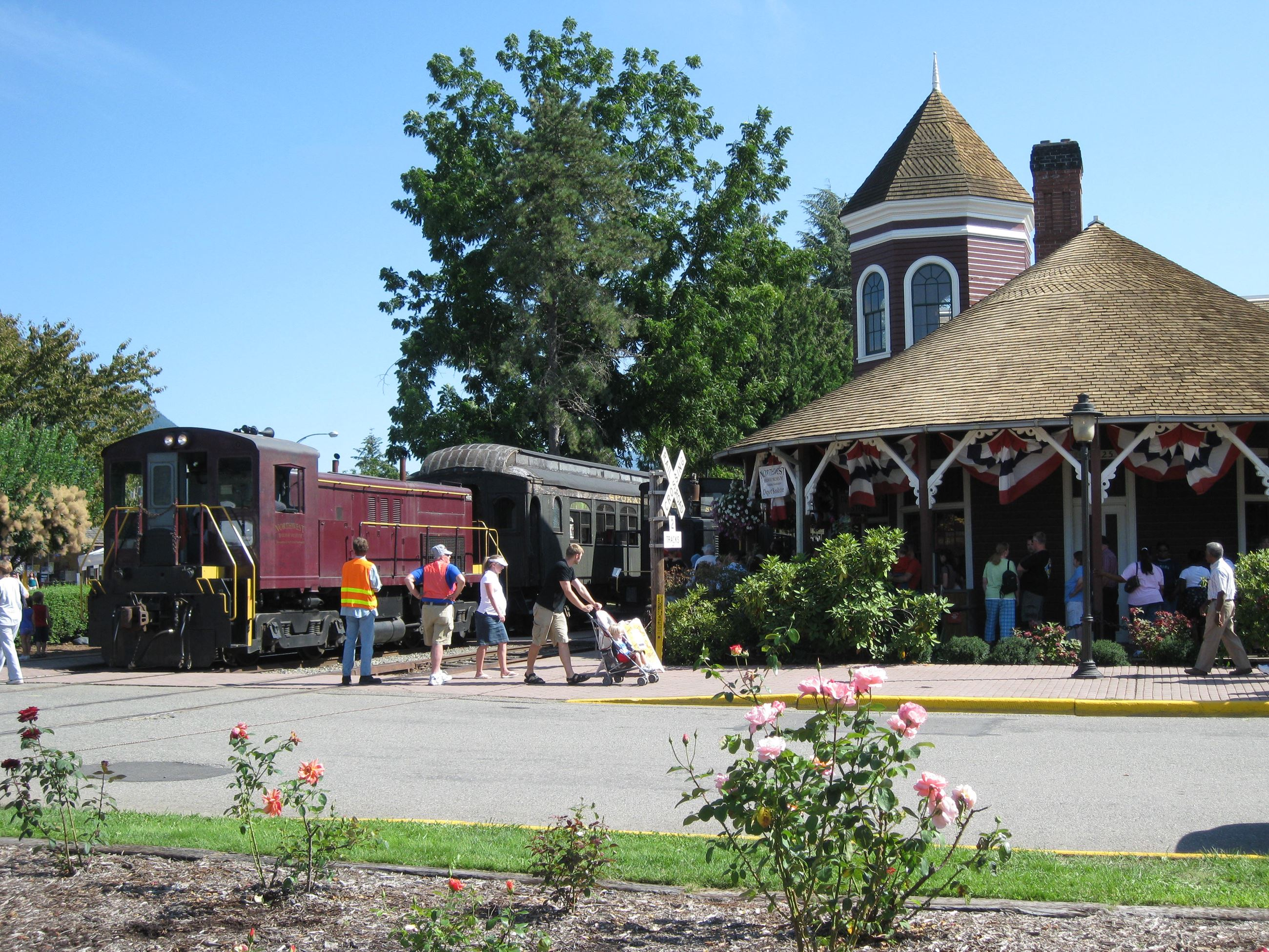 This is a picture of the Historic Snoqualmie Train Depot with the depot, a train, and several people