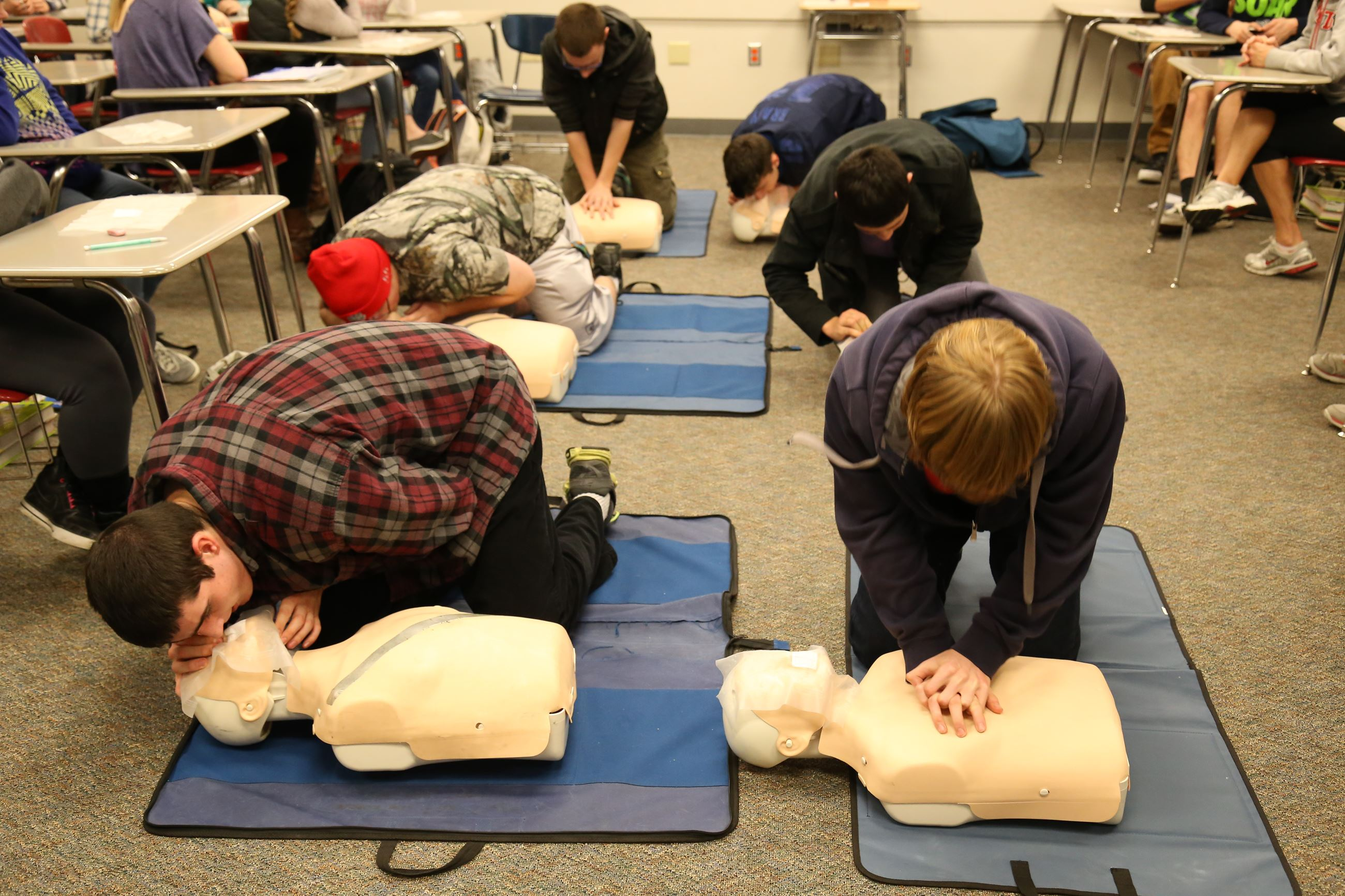 This is a photo of a high school boy practicing CPR.