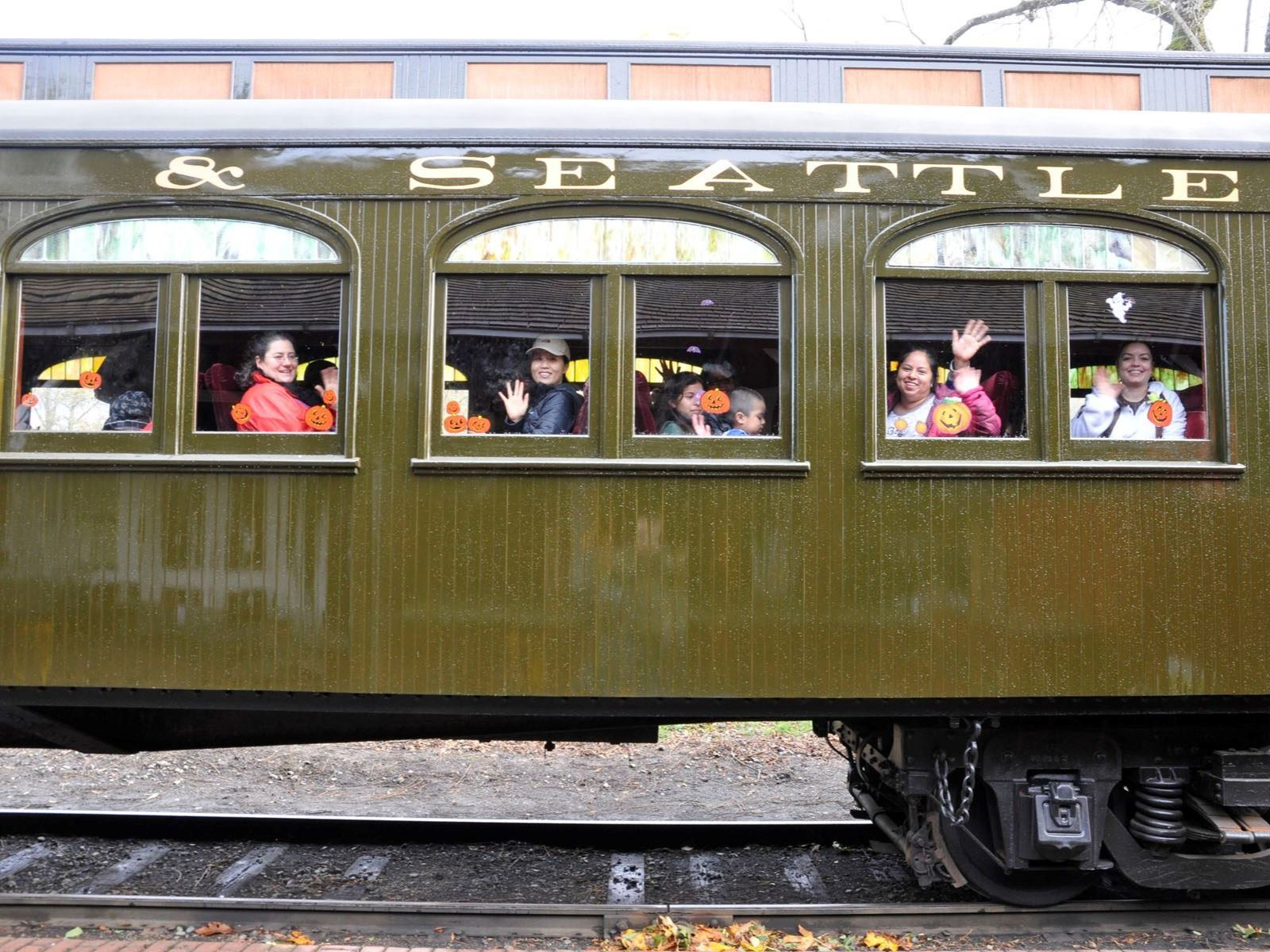 This is a picture of an antique train car with children waving.