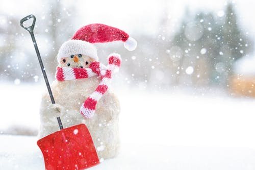This is a picture of a snowman with a snow shovel.