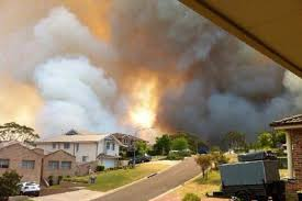 This is a picture of a wildland fire by houses.